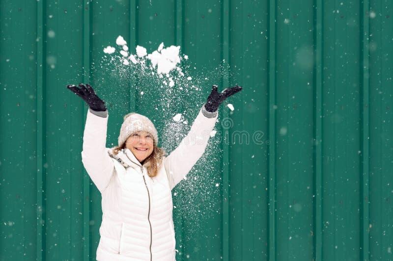 Снег счастливой женщины бросая в воздух стоковое изображение rf