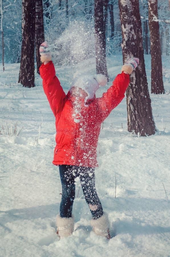Снег счастливой девушки бросая в воздухе на солнечный день стоковое фото