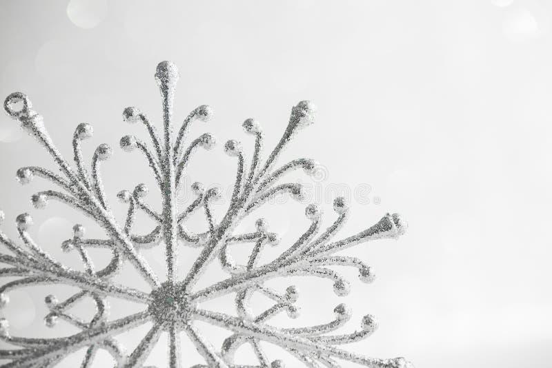 Снежинка рождества серебряная на абстрактной белой предпосылке праздника яркого блеска стоковые фото