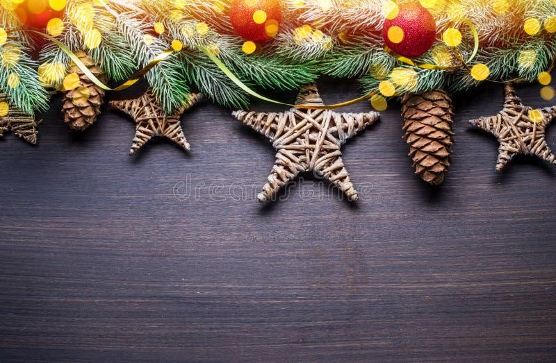Снежная ветвь с огурцами и размытыми рождественскими огнями с декором на деревянном столе Рождественские или новогодние праздники стоковые изображения