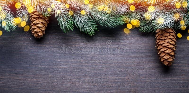 Снежная ветвь с огурцами и размытыми рождественскими огнями на деревянном столе Фон праздника Рождества или Нового года стоковое фото