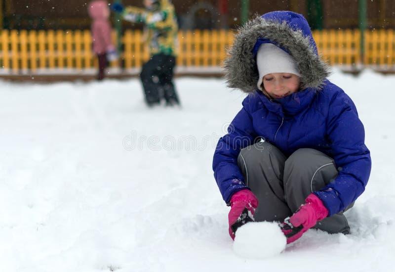 Снежный ком завальцовки маленькой девочки в зиме стоковое фото