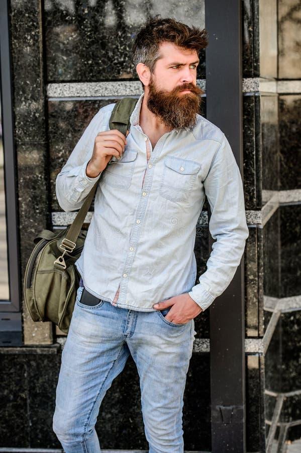 Снесите вещи в большой сумке на плече Мышечный человек с бородой и усик нося большую sporty сумку Путешествовать и стоковое фото