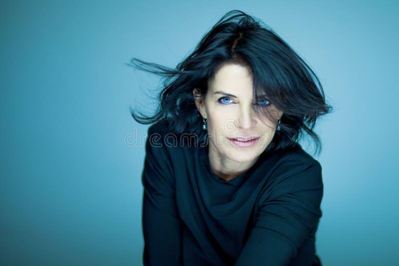 Сногсшибательная красивая и самоуверенная середина постарела женщина с черными волосами стоковые фотографии rf