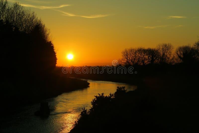 Сногсшибательный желтый заход солнца на реке Кларе Co Голуэй стоковое изображение