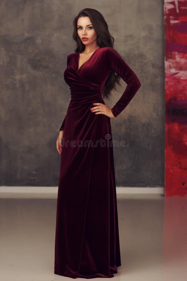 Сногсшибательная девушка в платье красного цвета вишни стоковое фото rf