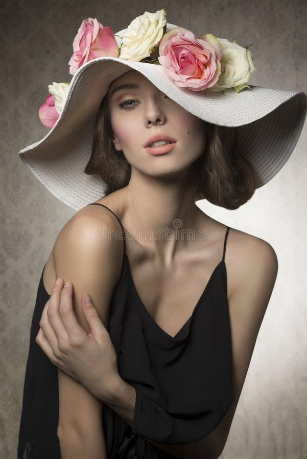 Сногсшибательная девушка с цветками на шляпе стоковая фотография