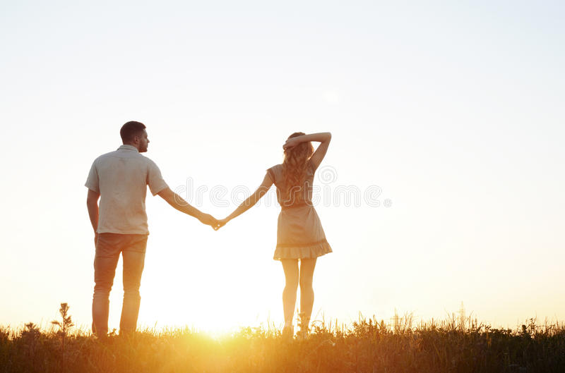 Сногсшибательные чувственные молодые пары в влюбленности представляя в лете field на стоковое фото