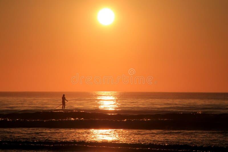 Сногсшибательный восход солнца при затвор отдельного человека всходя на борт над спокойным океаном мочит стоковые фотографии rf