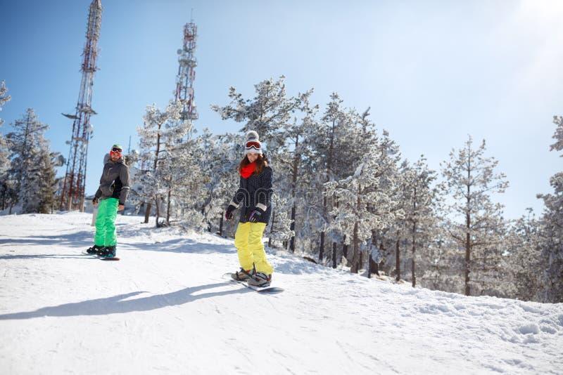Сноубординг женщины и человека в горе стоковое фото rf