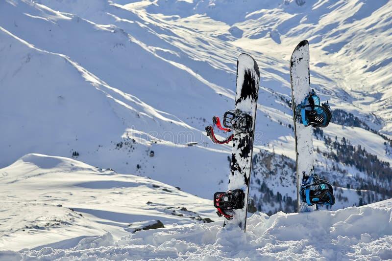 Сноуборд в снеге на наклоне -piste на день солнца между горами на предпосылке стоковые фото