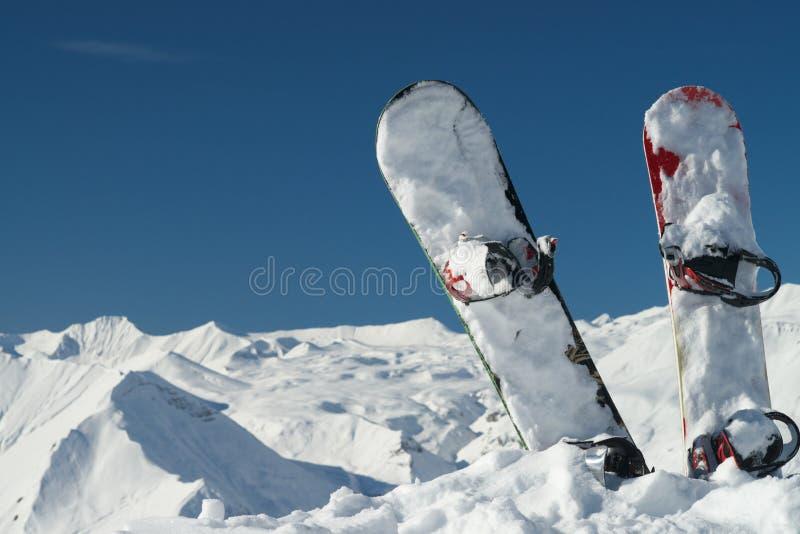 Сноуборды в снежных горах стоковое изображение