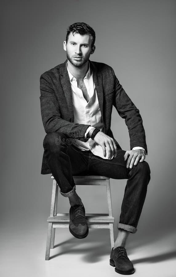 Снятая мода студии: портрет красивого молодого человека в джинсах, рубашке и куртке сидя на стенде черная белизна стоковая фотография rf