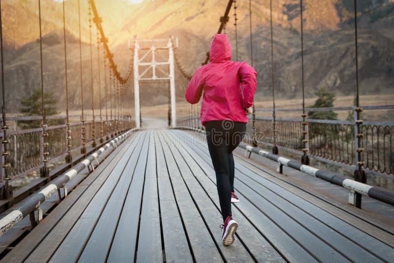 Снятый красивой тренировки взрослой женщины на восходе солнца стоковые фото