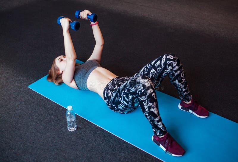 Снятый молодой женщины работая с гантелями на спортзале Мышечная женская тренировка на циновке тренировки внутри стоковое изображение