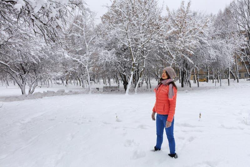 Снятый счастливой и стильной красивой женщины в яркой куртке коралла и голубых джинсах, усмехающся, наслаждаясь зимним днем стоковые фото