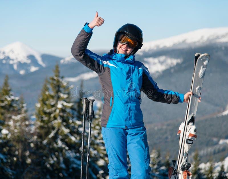 Снятый счастливый женский нося показывать шестерни катания на лыжах усмехаясь thumbs вверх по представлять в горах стоковое фото