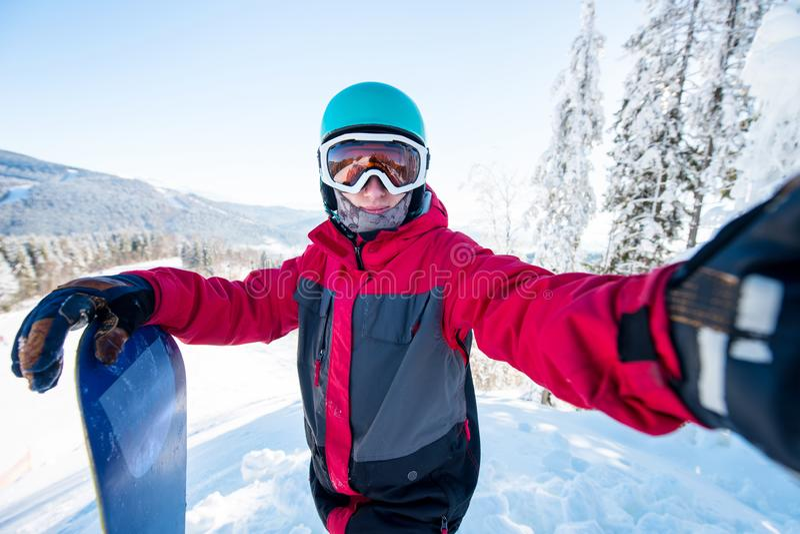 Снятый snowboarder человека принимая selfie, нося шлем, маску катания на лыжах и красочную одежду сноуборда зимы стоковое изображение rf