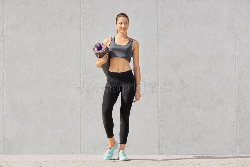 Снятый sporty дамы фитнеса в вскользь верхней части, гетры и тапки, готовые для разминки держат циновку тренировки, над серым con стоковая фотография