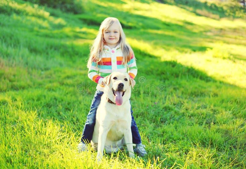 Собака ребенка и retriever labrador на траве в лете стоковое фото