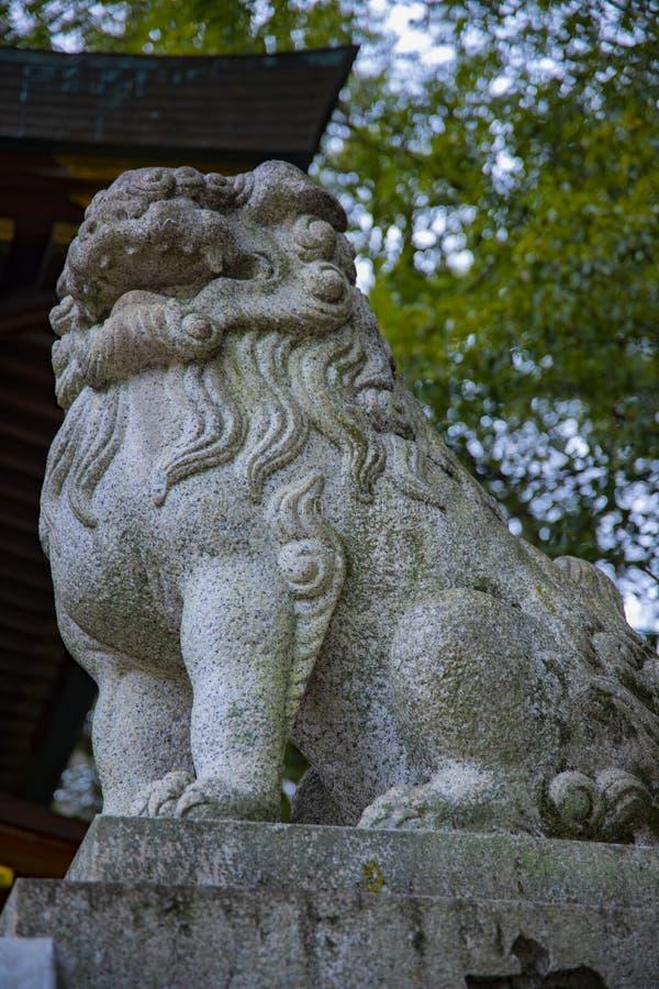 Собака KOMAINU попечителя статуи на японской традиционной святыне стоковое фото