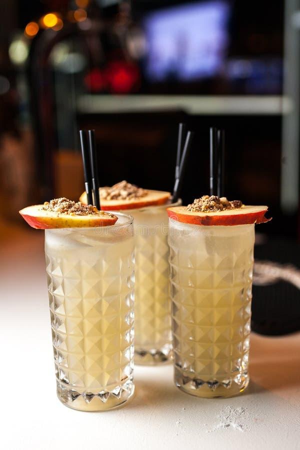 Соберите оранжевые коктеили с яблоком и cinamon на белом баре стоковая фотография