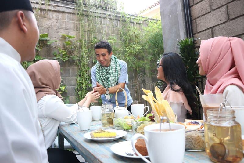 Соберите счастливое молодое мусульманское приветствие в обедающем таблицы стоковые изображения rf