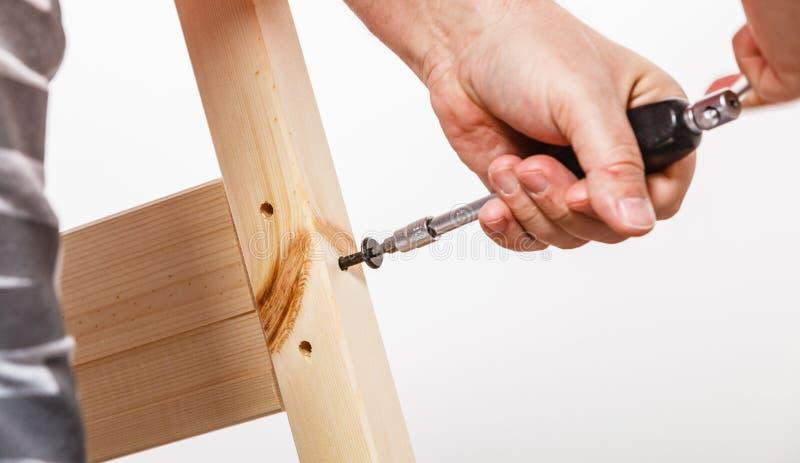 Собирая деревянная мебель используя scredriver Сделай сам стоковое фото rf