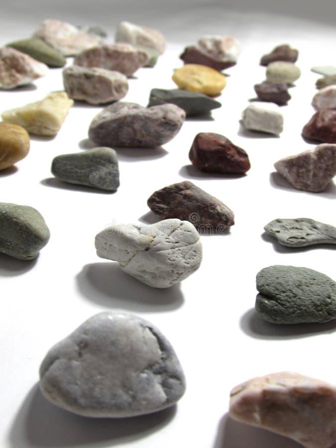 Собрание лежать в строках пестротканых небольших естественных камней минералов, лежа на белой предпосылке стоковое фото