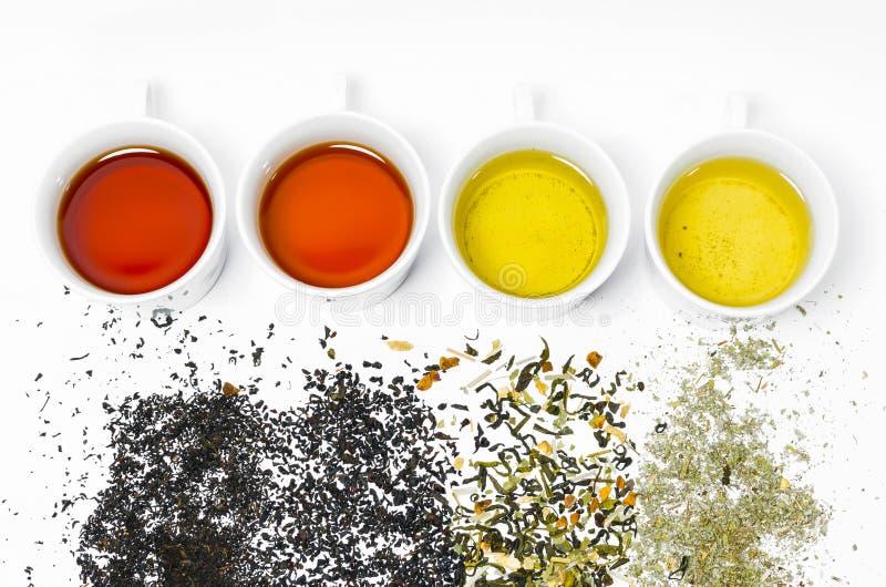 Собрание различных чаев в чашках с листьями чая на белой предпосылке стоковое изображение