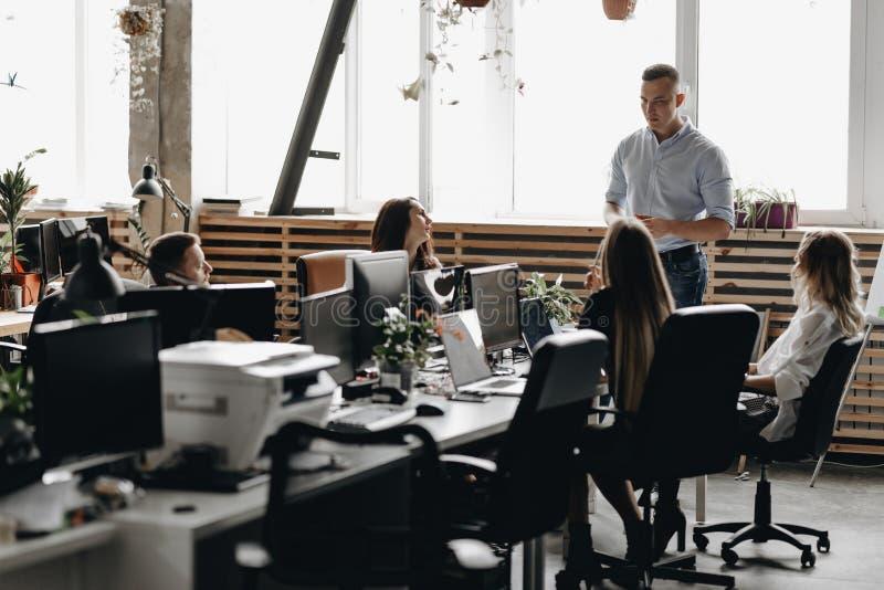 Собрание сотрудников молодой успешной команды в светлом современном офисе оборудованном с современными конторскими машинами стоковые изображения rf