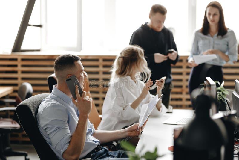 Собрание сотрудников молодой успешной команды в светлом современном офисе оборудованном с современными конторскими машинами стоковое фото