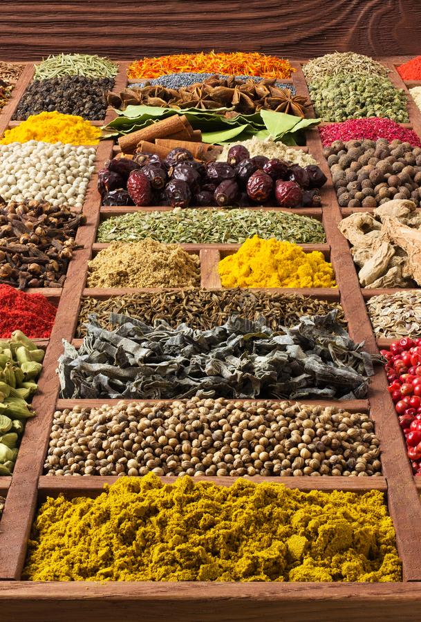 Собрание специй и трав в деревянном подносе Красочные condiments как предпосылка для дизайна пакуя с едой Различная приправа стоковое изображение