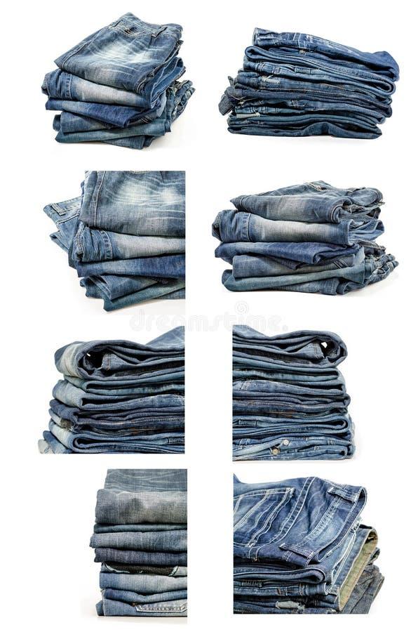 Собрание сложенных старых голубых джинсов изолированных на белизне стоковая фотография rf