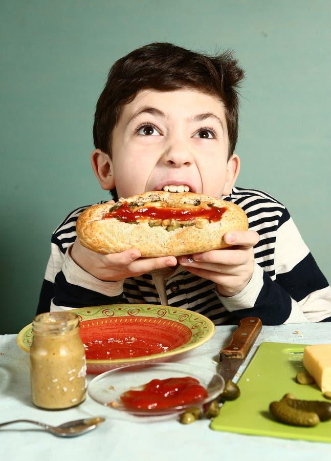 Собственная личность укуса мальчика сделала огромную горячую сосиску стоковая фотография rf