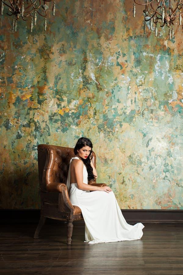 Совершенная женщина в белом платье ослабляя на кресле стоковое изображение rf