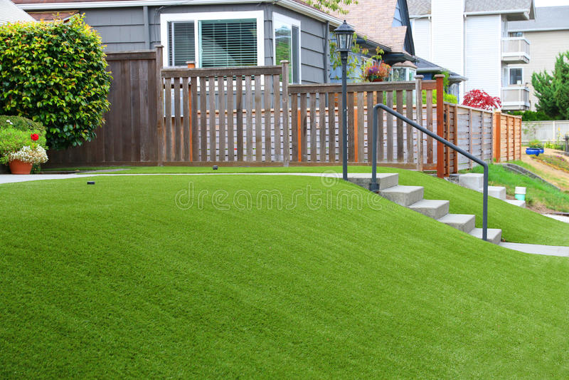 Совершенная трава благоустраивая с искусственной травой в жилом районе стоковые фотографии rf