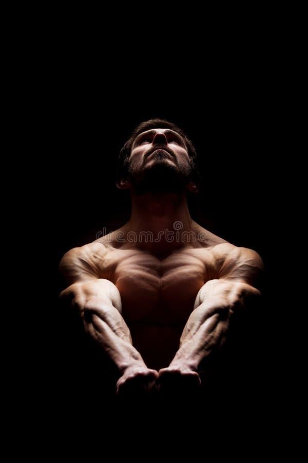 Совершенное тело и сильная концепция разума Мышечный человек держа его руки совместно и смотря вверх драматический свет стоковые фотографии rf