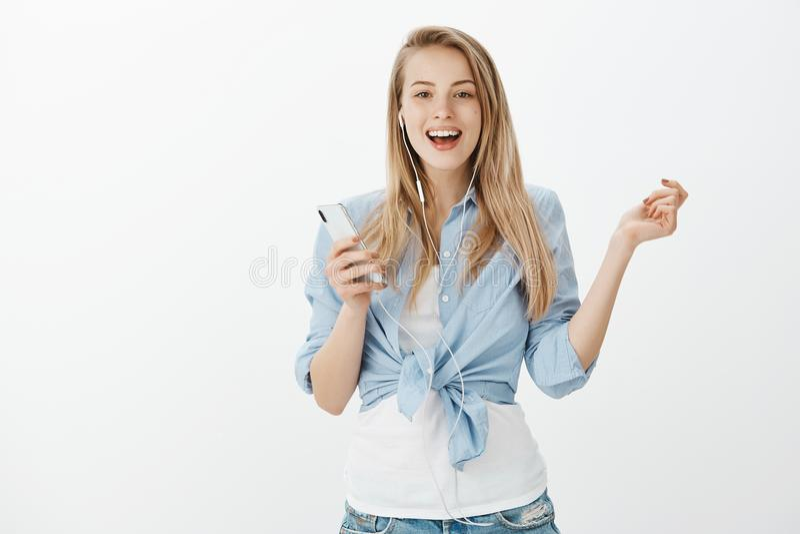 Совершенный день для петь вперед Крытая съемка положительное симпатичное европейское женского, держа smartphone и слушая стоковые фотографии rf