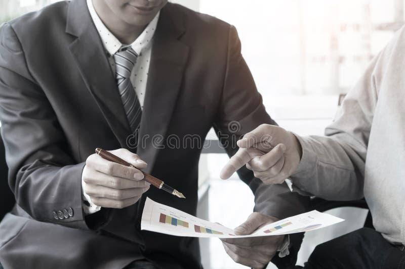 Советник дела анализируя финансовые диаграммы обозначая progre стоковая фотография rf