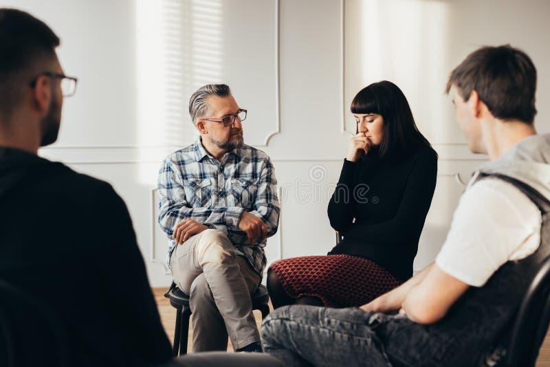 Советник школы говоря с подавленным подростком во время терапии группы стоковая фотография