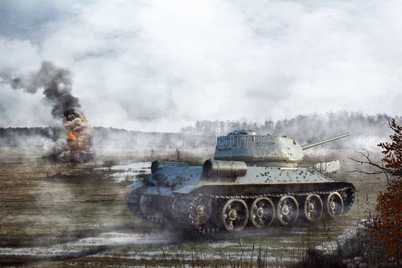 Советский танк идет через болото на заднем плане горящего танка стоковые фото