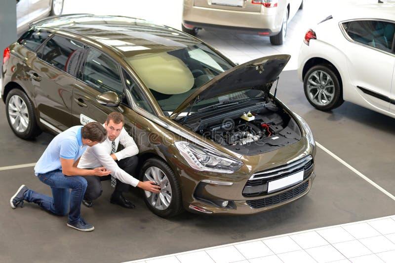Совет автосалона - продавцы и клиенты покупая автомобильную беседу технологии о автошинах стоковое изображение rf
