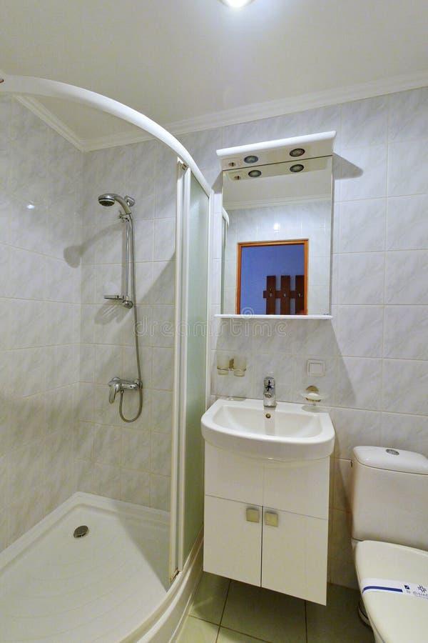 Совмещенная ванная комната с реновацией Европейск-качества положенной вне с белыми плитками протянула ливень потолка и современно стоковая фотография