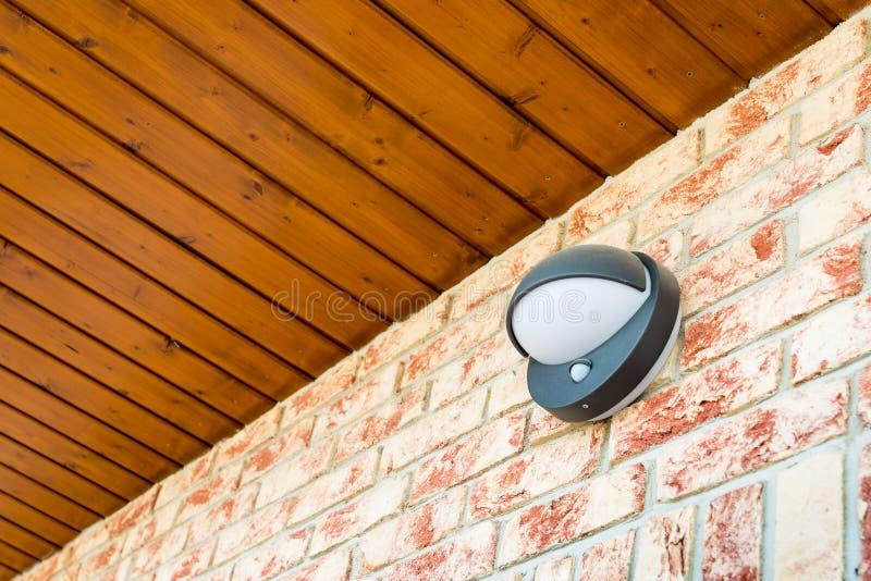 Современная лампа стены с датчиком движения и света на кирпичной стене стоковое изображение