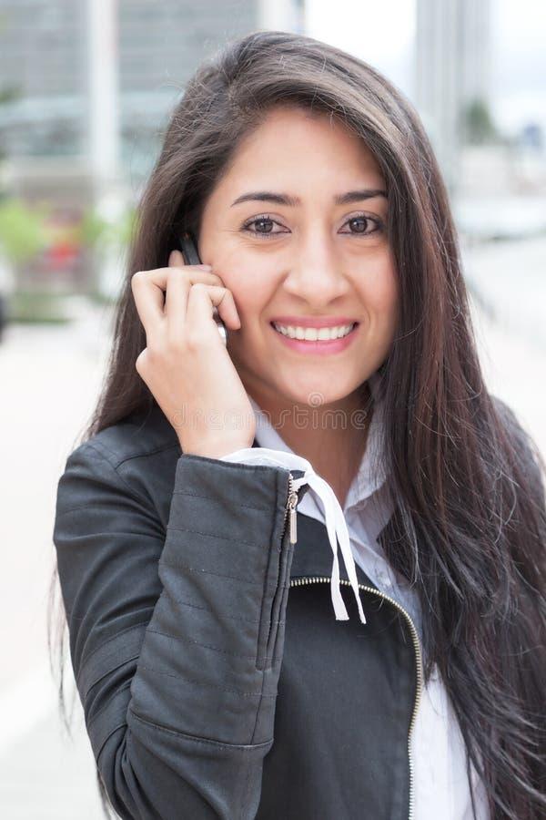 Современная латинская женщина с телефоном в городе стоковая фотография