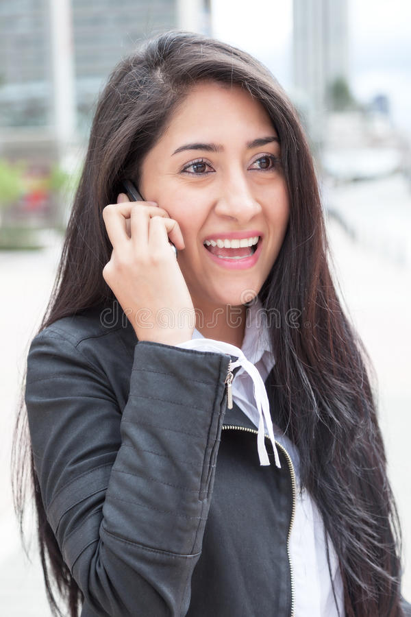 Современная латинская женщина с телефоном в городе стоковые изображения
