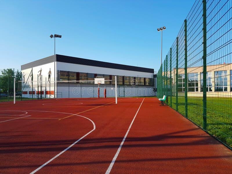 Современная баскетбольная площадка в дворе начальной школы Многофункциональная спортивная площадка ` s детей при отделанное повер стоковые изображения rf