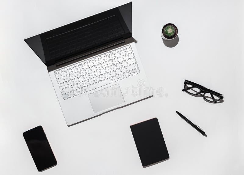 Современная белая таблица стола офиса с компьтер-книжкой, телефоном пустого экрана умным, стильными eyeglasses, черной тетрадью и стоковые фотографии rf