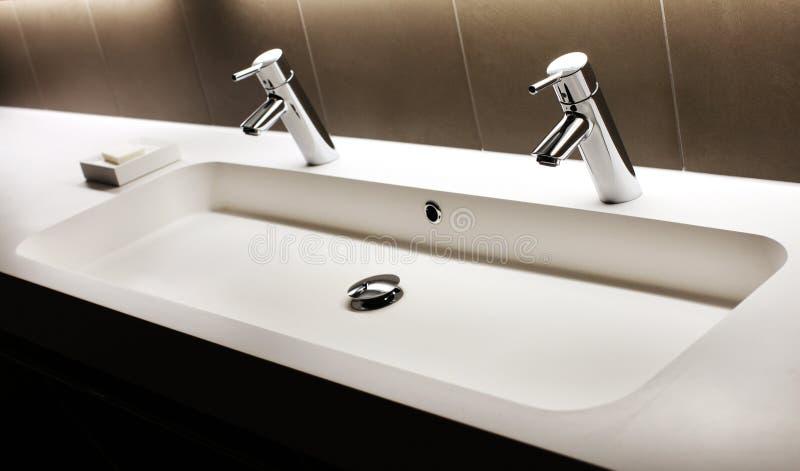 Современная белая раковина с 2 сияющими faucets, кран стоковые изображения